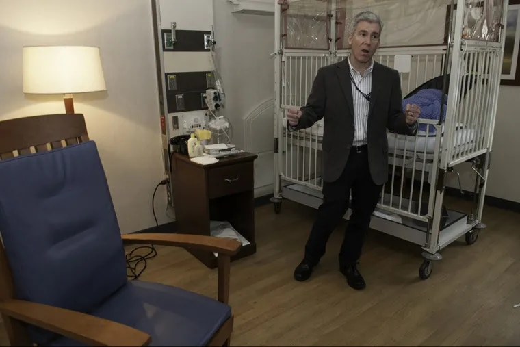 """Crozer-Chester Medical Center pediatrician Robert Noll in front of the crib of an infant born dependent on his mother's opioids. """"Sometimes,"""" he said, """"babies go home to desperate situations."""""""