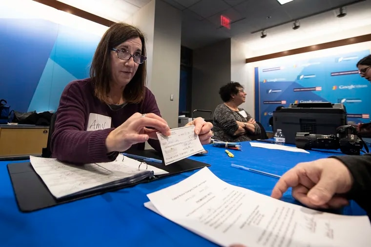 Amy Krulik,  president of the Hebrew Free Loan Society of Greater Philadelphia, awards a no-cost, short-term loan check to an unidentified applicant Sunday at the National Constitution Center.