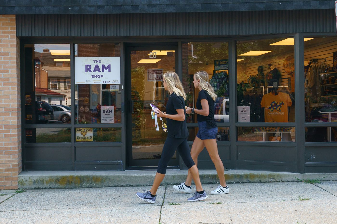 Pedestrians walk past the Ram Shop, a new convenience store on West Chester University's campus, which is staffed in part by students who have autism.