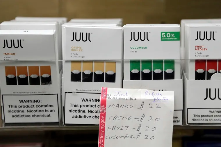 FILE - In this Thursday, Dec. 20, 2018 file photo, Juul products are displayed at a smoke shop in New York. On Thursday, Oct. 17, 2019, the company announced it will voluntarily stop selling its fruit and dessert-flavored vaping pods.