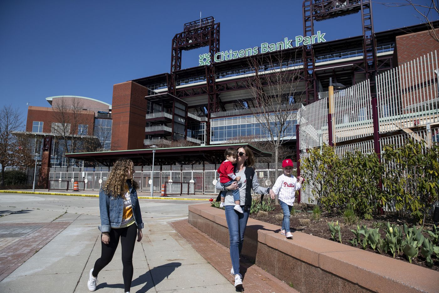 """Regan Lamb, from Northeast Philly, John Sosalski, 16 months, Rachel Sosalski, from Fishtown, and Ava Sosalski, 3, walk outside of Citizens Bank Park on what was supposed to be the Philadelphia Phillies Opening Day on Thursday. """"We would be here as a family if it weren't for this situation,"""" Sosalski said. On March 16, the Major League Baseball announced that the start of the season would be delayed following CDC guidelines to slow the spread of the coronavirus."""