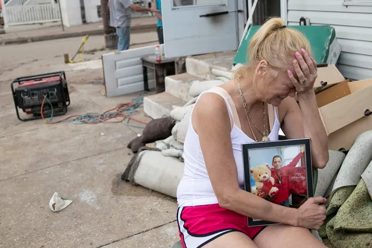 Laura Sinnott Caroluzzi tears up while she holds a photo of her husband, Jack Caroluzzi, who died in Wednesday evening's flooding, outside of their home in Bridgeport, Pa.