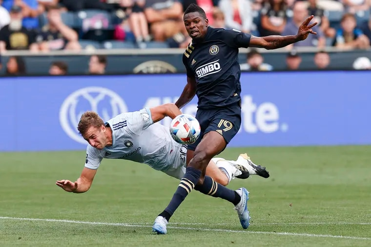 Union forward Cory Burke runs after the soccer ball past Fire defender Wyatt Omsberg.