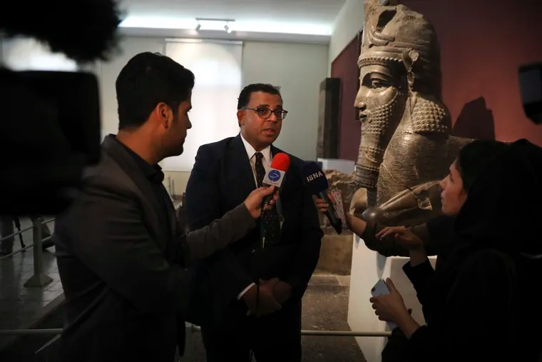 Christopher Woods, center, speaks with journalists in 2019 during a ceremony to unveil ancient clay tablets that were returned to Iran by the University of Chicago's Oriental Institute.  (AP Photo/Vahid Salemi)