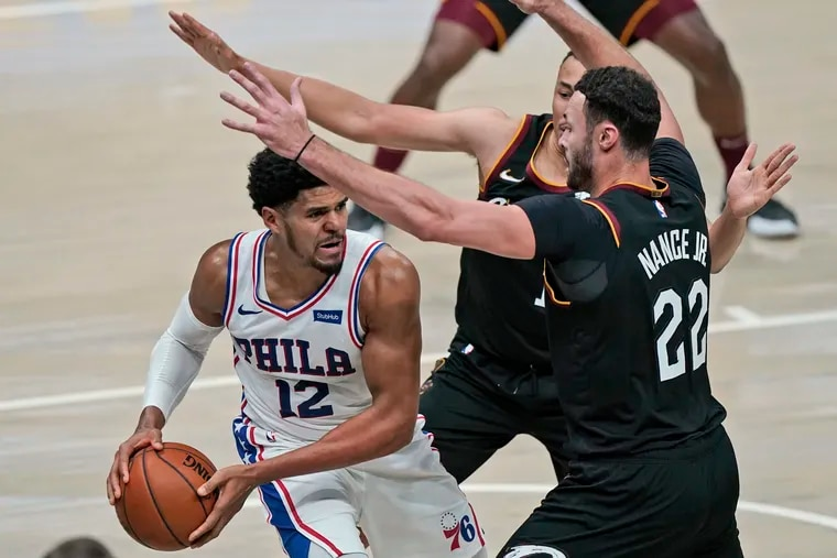 The 76ers' Tobias Harris (12) tries to get past Cleveland Cavaliers' Dante Exum (1) and Larry Nance Jr. in the second half.