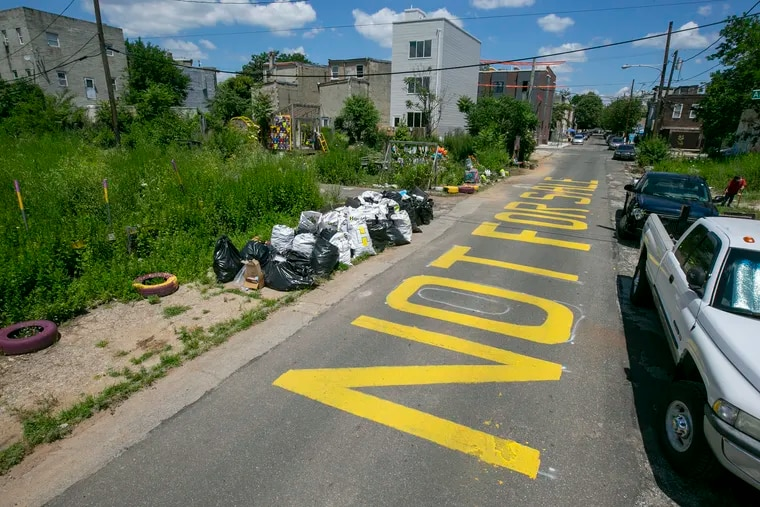 """""""Not for Sale"""" is painted on the street near the Cesar Andreu Iglesias Community Garden, seen in a 2020 file photograph. It's one of hundreds of gardens, side yards and other properties imperiled by the continuing fallout of a 24-year-old city effort to raise funds by selling delinquent tax liens."""