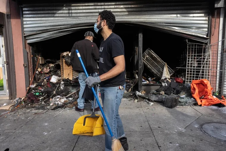 Community members clean up damage and vandalism last June at a store that was burned on 52nd Street.