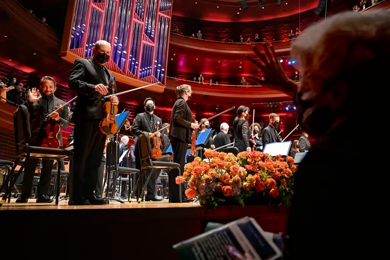 Usher Antoinette DuBiel (front) waves to violinists Richard Amoroso (rear, left) and William Polk as members of the  Philadelphia Orchestra walk onstage at Verizon Hall, on opening night at the Kimmel Center.