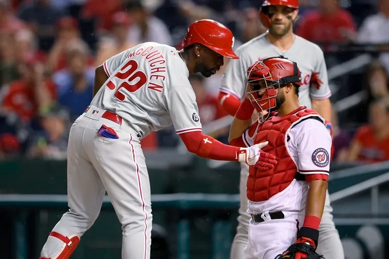 The Phillies' Andrew McCutchen taps Nationals catcher Keibert Ruiz on the chest protector as he comes home on his two-run homer during the fourth inning.