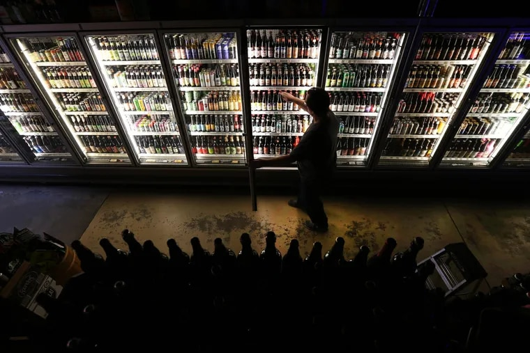 Mike Kellett, owner of Bottle Bar East at 1308 Frankford Avenue, straightens up the beers in his massive display case on February 8, 2016 in Philadelphia, Pa.