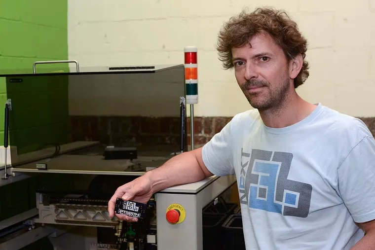 Evan Malone, president of NextFab, with a Pick and Place Machine, which assembles such things as circuit boards.