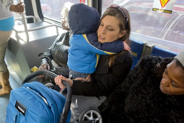 November 10, 2017 — Lacey Kohlmoos holds her 1-year-old son Finn Heckert and their folded up stroller while riding the bus. Kohlmoos has started a petition to ask SEPTA to allow parents to bring their strollers onto the bus unfolded. (Avi Steinhardt/ For the Philadelphia Inquirer)