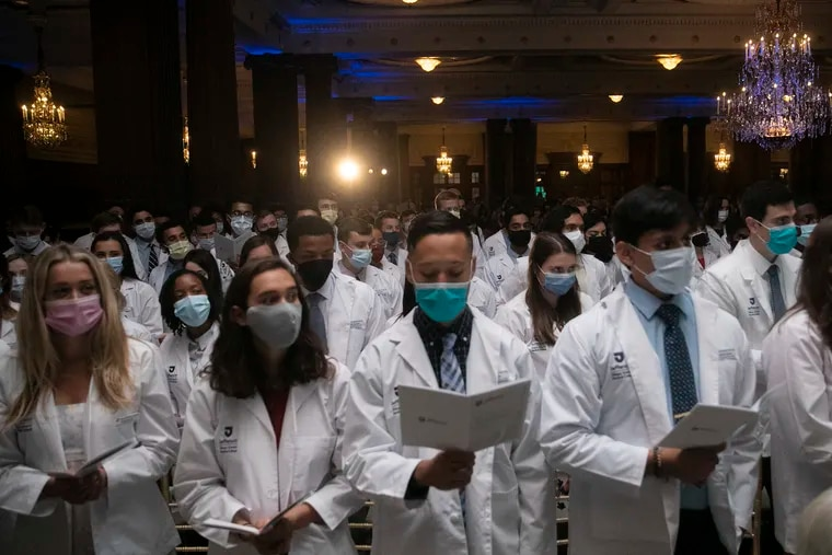 Sidney Kimmel Medical College students read the Hippocratic oath last month. All college students in Philadelphia will have to be vaccinated by October, the city announced today.