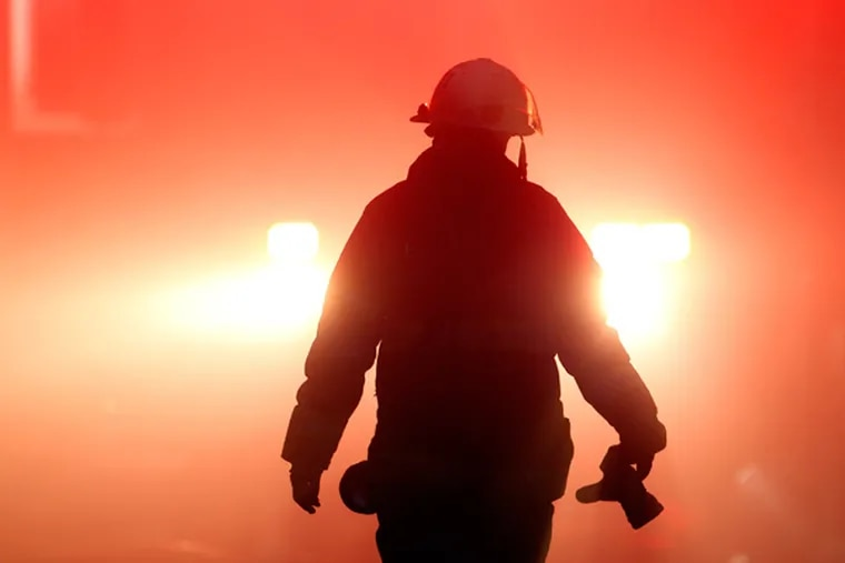 A firefighter walks through smoke from a fire Monday, Dec. 10, 2012, in Philadelphia. Fire Department Executive Chief Richard Davison says the blaze broke out Monday afternoon at a three-story industrial garage. Davison says an elderly woman has been taken to the hospital in stable condition. The woman's injuries were not immediately clear. (AP Photo/Matt Rourke)