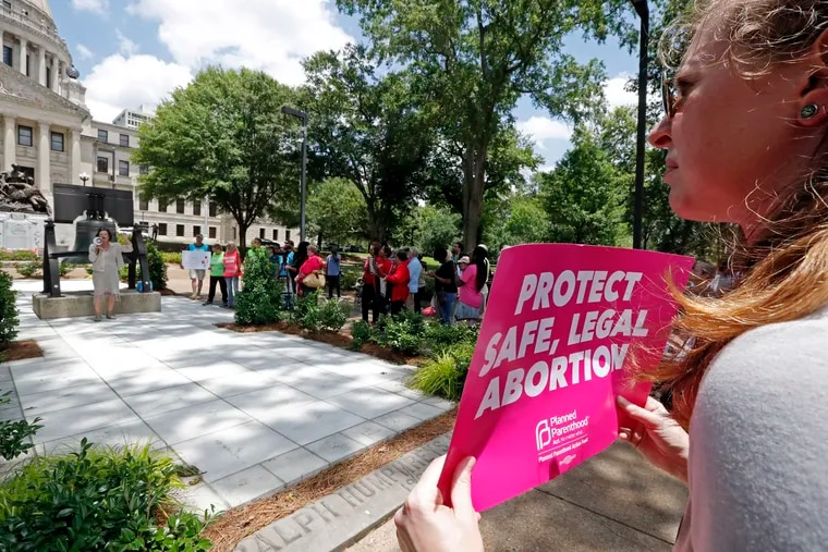 An abortion rights advocate holds a sign at the Capitol in Jackson, Miss., expressing opposition to a new state law that prohibits most abortions. The rally in Jackson was one of many around the country to protest abortion restrictions that states are enacting. (AP Photo/Rogelio V. Solis)