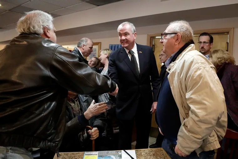 New Jersey Gov. Phil Murphy (center) shakes hands with patrons at the Ocean Bay Diner in South Amboy last month before a news conference about the minimum wage bill, which Murphy signed into law Monday.