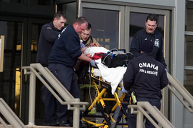 Paramedics rush a victim out of a store in Omaha, Neb. A gunman killed eight people and wounded five before shooting himself.