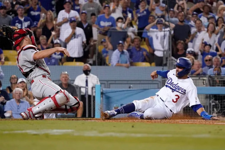 The Dodgers' Chris Taylor scored ahead of a tag from Phillies catcher J.T. Realmuto during a game in Los Angeles in June.