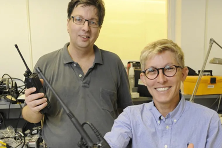 Sandy Clark (foreground), a Ph. D. graduate student in University of Penn's Computer and Information Sciences program, and Matt Blaze, Director of the Distributive Systems Lab, hold P25 two-way radios in their lab. (Clem Murray / Staff Photographer)