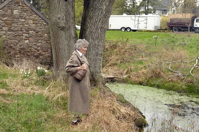 """Christine Fisher stands near a springhouse and pond on property near Skippack Pike where groundwater was contaminated because of a leak from a gas station. """"After a rain, we find these little puddles of sheen back in the woods here, still,"""" she said. (Ron Tarver / Staff Photographer)"""