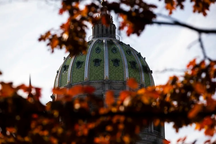The dome of the Pennsylvania Capitol is visible through the trees in Harrisburg, Pa.