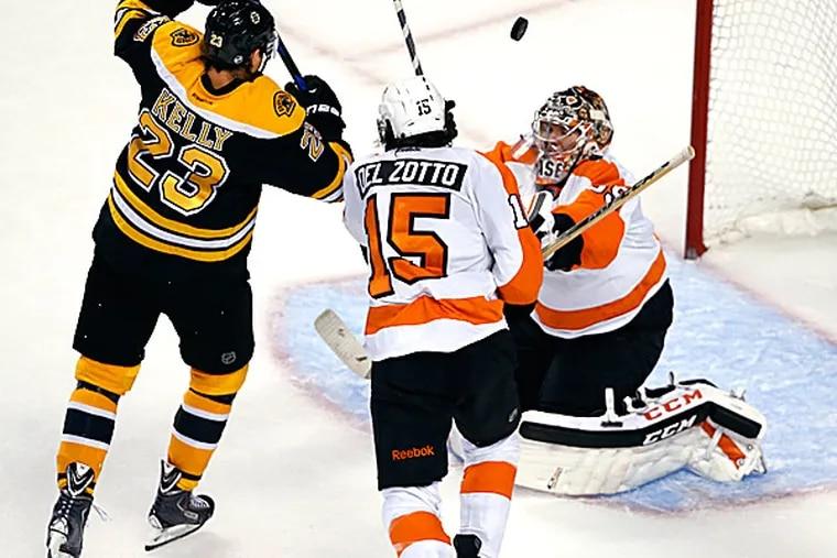 Bruins center Chris Kelly scores a goal against Flyers goalie Steve Mason as defenseman Michael Del Zotto tries to defend in the third period. (Elise Amendola/AP)