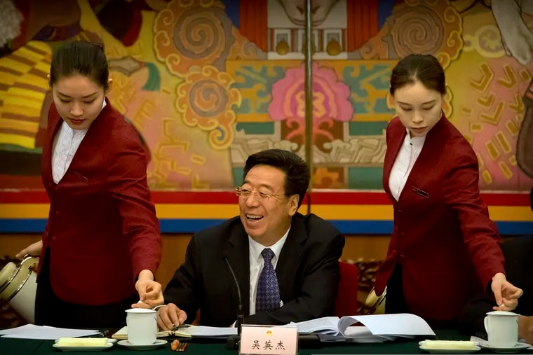 """Wu Yingjie, center, Communist Party secretary of the Tibetan Autonomous Region, laughs as attendants refill mugs of tea during a group discussion session held on the sidelines of the annual meeting of China's National People's Congress (NPC) in the Tibet Hall of the Great Hall of the People in Beijing, Wednesday, March 6, 2019. The Chinese Communist Party chief for Tibet said on Wednesday that the Dalai Lama has not done a """"single good thing"""" for the region. (AP Photo/Mark Schiefelbein)"""