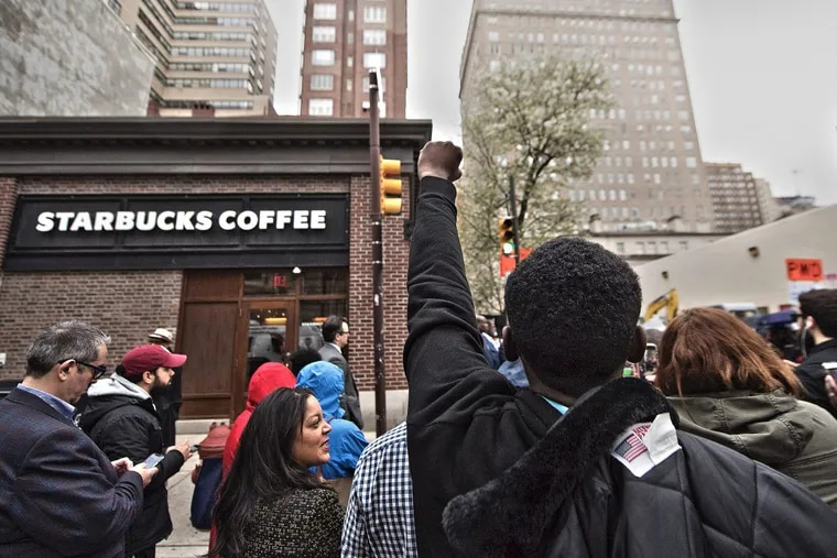 Christopher Potts, center, protest outside the Starbucks on 18th and Spruce Streets.