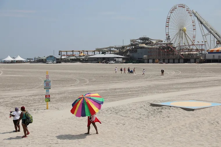 A woman carries an umbrella across the beach in Wildwood, N.J., on July 3.