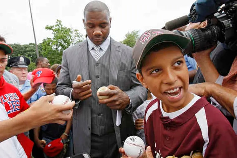 At Hunting Park, Phillies first baseman Ryan Howard signs balls, including one for Luis Santiago Jr. The Ryan Howard Family Foundation's first grant was a $50,000 contribution toward the park's restoration.