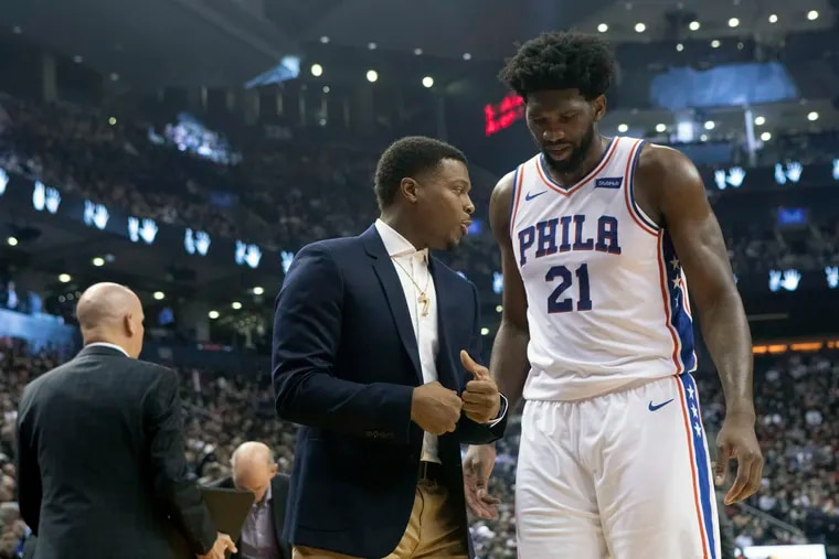 The 76ers' Joel Embiid (21) talks to the Toronto Raptors' Kyle Lowry after the Raptors defeated the 76ers in November 2019.
