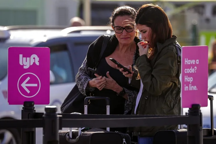 Denise Lyra (left) and her daughter Gabriela, arriving from Brazil, check her phone to figure out from where to get their ride at the pickup lot at Los Angeles International Airport in November 2019.