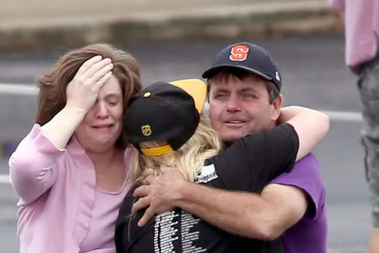 A FedEx worker (right) is consoled as others wait to reunite with relatives. The shooter, a 19-year-old package handler, is believed to have killed himself.