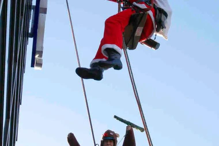 JUNJI TSUDA (top) and Akihiro Kondo dress as Santa Claus and reindeer as they wash windows at a Tokyo mall yesterday.