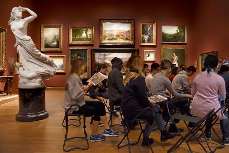 """First-year Penn medical students sharpen their observation skills at the Philadelphia Museum of Art, overseen by a marble sculpture, """"The Lost Pleiad,"""" by Randolph Rogers."""