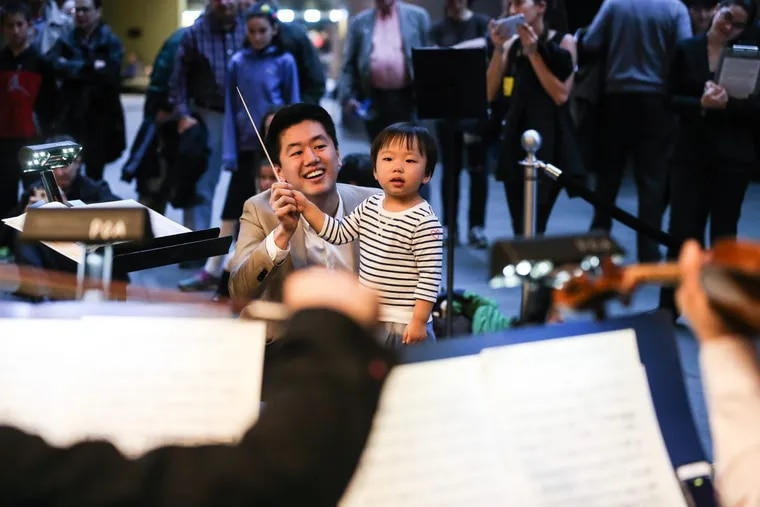 Assistant Philadelphia Orchestra conductor Kensho Watanabe helps three-year-old Grace Gu from Phoenixville conduct during a conduct-along at the Kimmel, February 28, 2017.
