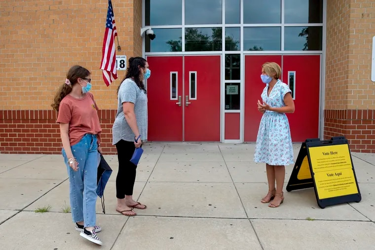 Amy Kennedy, then a Democratic candidate for New Jersey's 2nd Congressional District, greets voters Karen Leonard and her daughter Katie, 14, on primary election day July 7, 2020, outside the Northfield Community School, where Kennedy worked as a teacher. Katie was picking up her eighth-grade graduation material.