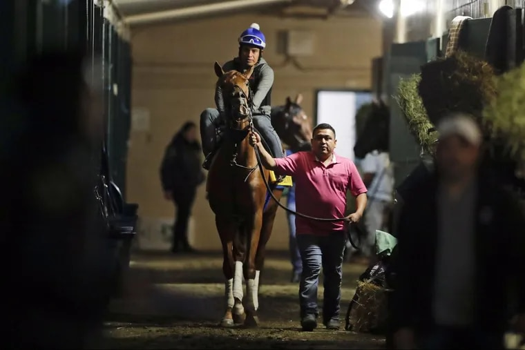 Angel Garcia rides Gun Runner as they make their way toward the track during workouts before the Breeders Cup races at Del Mar.