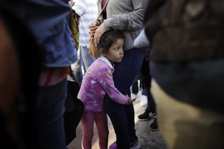 Nicole Hernandez, of the Mexican state of Guerrero, holds on to her mother as they wait with other families to request political asylum in the United States, across the border in Tijuana, Mexico, on Wednesday, June 13, 2018. The family has been waiting for about a week in this border city hoping for a chance to escape widespread violence in their home state. (AP Photo/Gregory Bull)