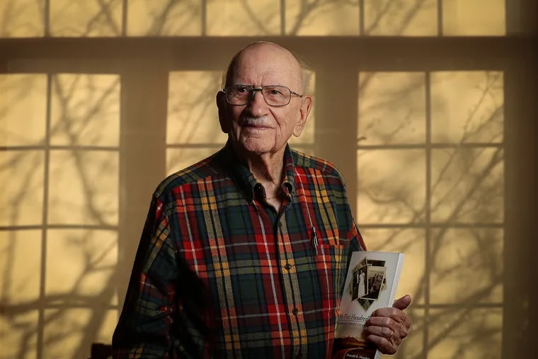 """Donald R. Fletcher, 101 years-old, who lives in the Lions Gate retirement community, poses for a portrait in Voorhees Township, NJ on January 15, 2020. He is holding a copy of his recently published book, """"My First 100 Years: A Life on Three Continents."""""""