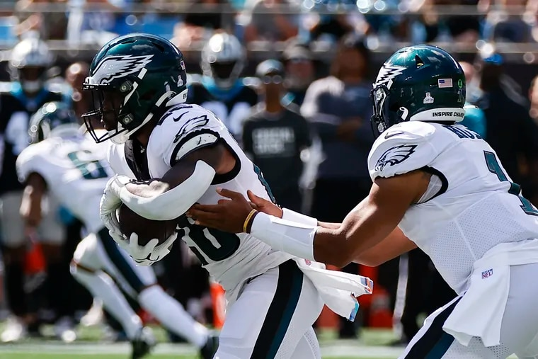 Eagles running back Miles Sanders takes the football from quarterback Jalen Hurts against the Carolina Panthers on Sunday in Charlotte.