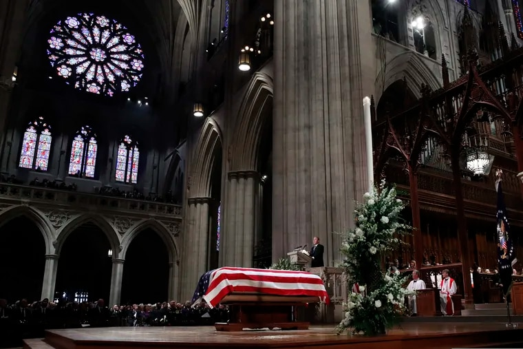 Former President George W. Bush speaks in front of the flag-draped casket of his father, former President George H.W. Bush, at the State Funeral at the National Cathedral Wednesday in Washington.