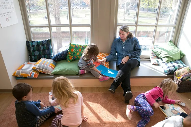 Jen Sharp, an early education program teacher, back right, reads books with students at the new  Germantown Friends School site in the Curtis Center, overlooking Washington Square.  JESSICA GRIFFIN / Staff Photographer