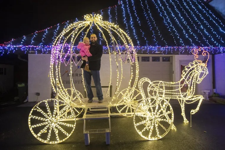 Nick McKelvey holds onto his daughter, Kaylee McKelvey, 2 1/2 years, while they get their photograph taken in the CInderella Carriage at Jack Yoast's front yard Christmas display in Ambler.