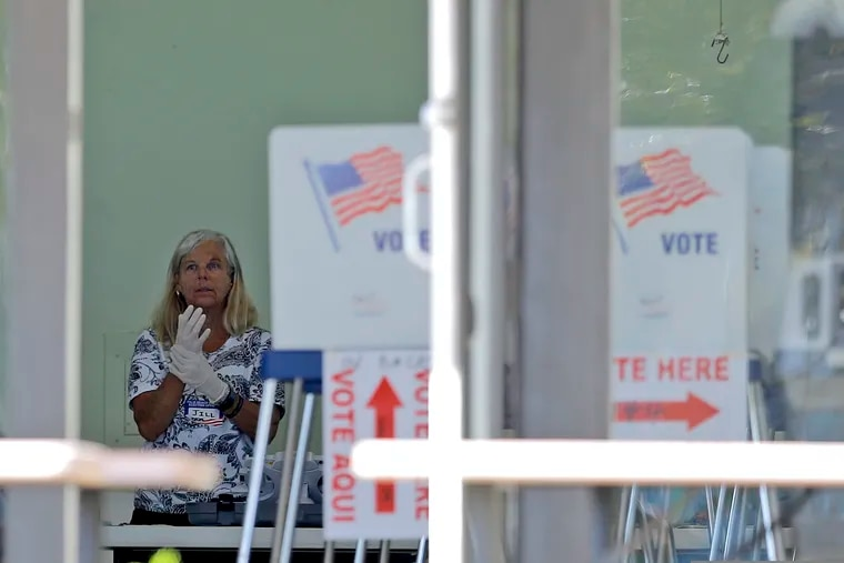 A polling place worker adjusts gloves as she tends to a reception table during the Florida primary election at the First United Methodist Church, Tuesday, March 17, 2020, in Jupiter, Fla. As Florida officials try to contain the spread of the novel coronavirus, the state's voters headed to the polls to cast ballots in the Democratic presidential primary. (AP Photo/Julio Cortez)