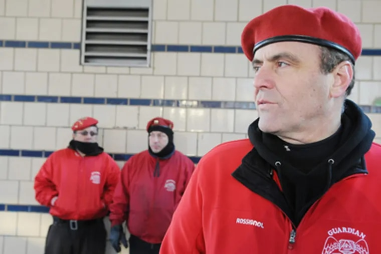 The Guardian Angels' Curtis Sliwa patrols at the corner of Kensington and Somerset streets. The Angels are passing out flyers with a photo of an alleged killer on the loose. (Sarah J. Glover / Staff Photographer)
