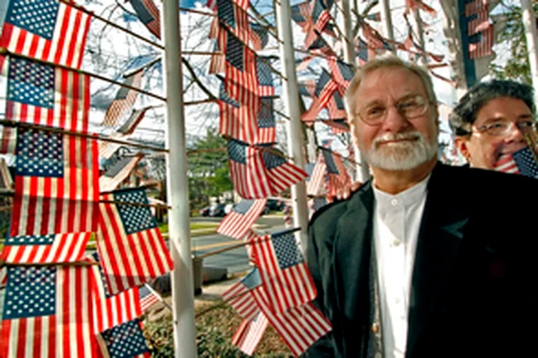 Cherry Hill architect Michael Bloom and assistant Louie Reisser fly a flag for each service member killed in Iraq.