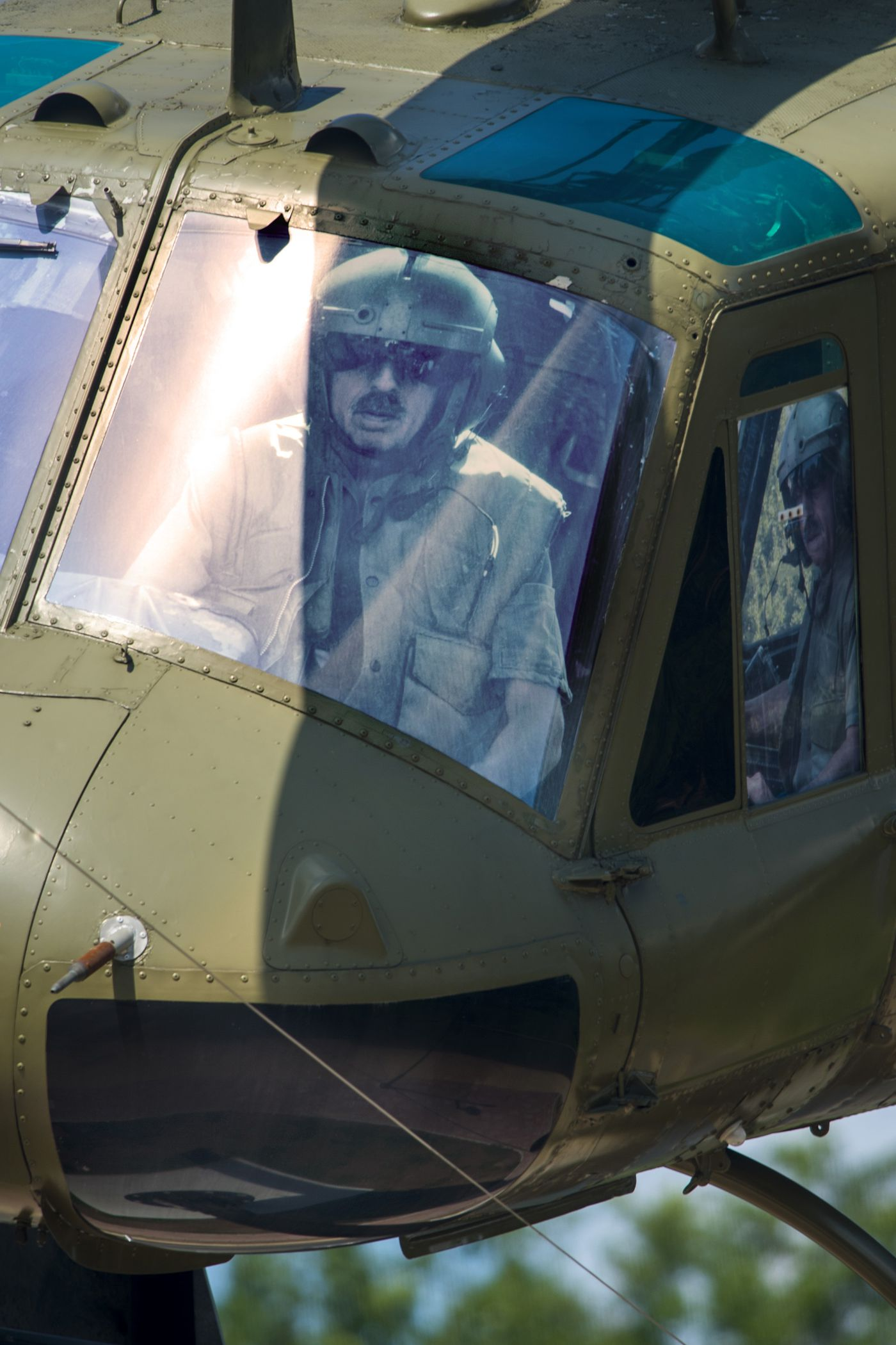 A life-size contemporary photograph of Ralph Storti is in the cockpit of the Huey helicopter. Other community members are pictured in other windows of the chopper.