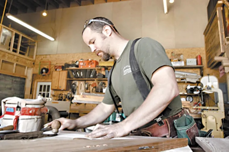 Brendan Isaac Jones, center and his craftsmen work on reclaimed wood projects at Greensaw Design & Build. (David Swanson / Staff Photographer)