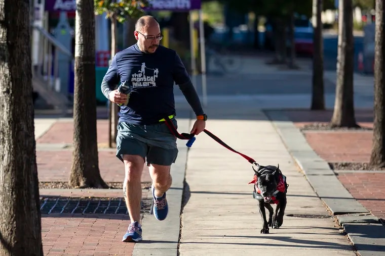 """Guillermo Torres, 35, of Acapulco, Mexico, volunteer at Street Tales Animal Rescue with the Monster Milers, takes Sweet Dee, a 7-year-old Pit Bull mix, on a run along Columbas Blvd., on Saturday, Oct. 19, 2019. """"For me volunteering is a good way to help,"""" Torres said. """"Many people like to help and volunteering is a very important and rewarding thing to do. It's really close to my heart."""""""